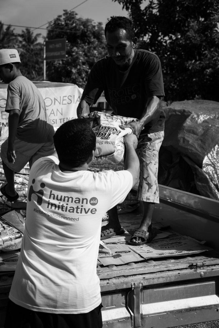 Human Aid Initiative staff carrying food aid