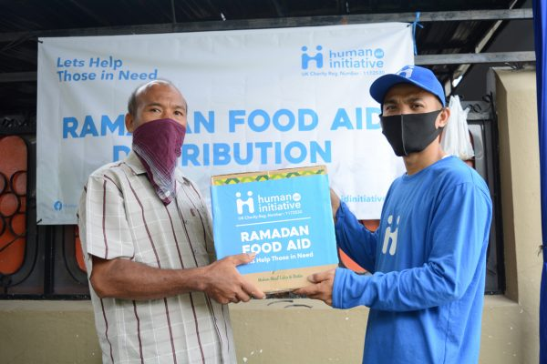 Two males holding food aid box